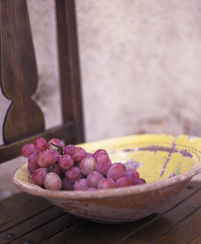 Dish of red grapes on a wooden chair