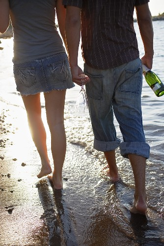 Young couple with bottle of sparkling wine & glasses on beach