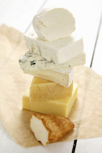 Pieces of different cheeses, stacked on paper