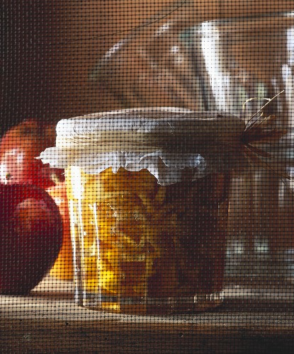 Caramelised apple preserve in a glass jar behind a fly screen