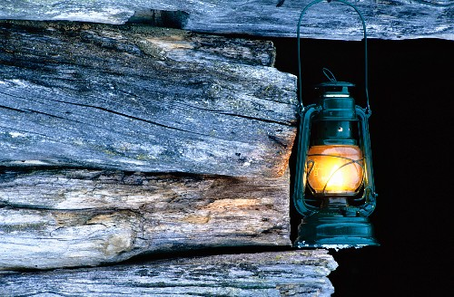 An oil lamp hanging from a wooden beam