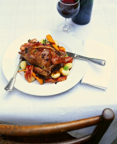 Roast pigeon with bacon and juniper on bed of vegetables