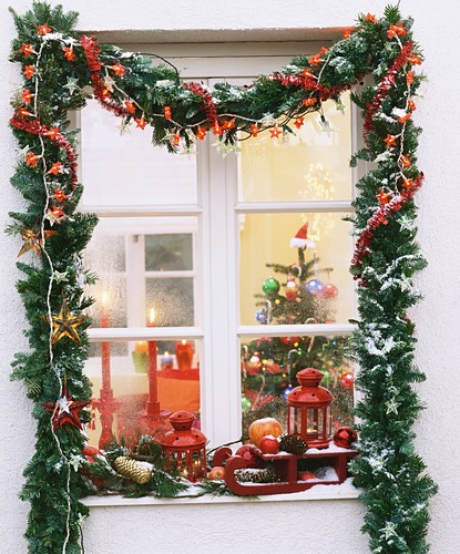 Christmas window with garland of greenery and fairy lights