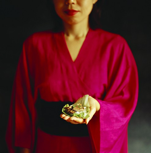 Woman in Japanese kimono presenting Korean dish