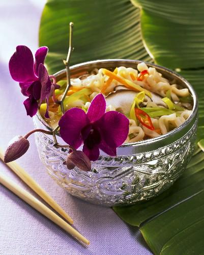Asian noodle soup with orchids
