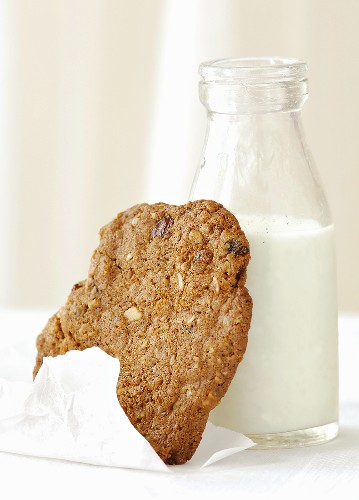 Raisin cookie leaning against a bottle of milk