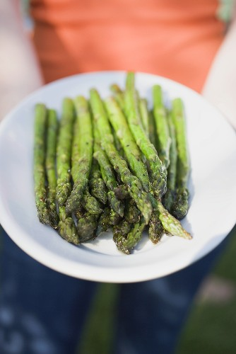 Woman holding plate of grilled asparagus