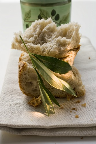 Pieces of white bread on linen cloth with olive sprig