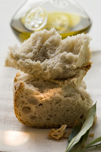 Pieces of white bread on linen cloth with olive sprig, olive oil