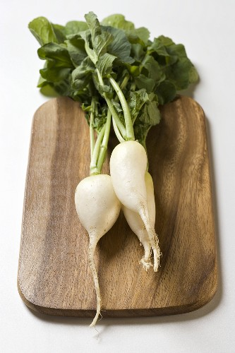 White icicle radishes with leaves on chopping board