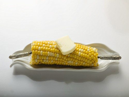 Corn cob with knob of butter in white dish