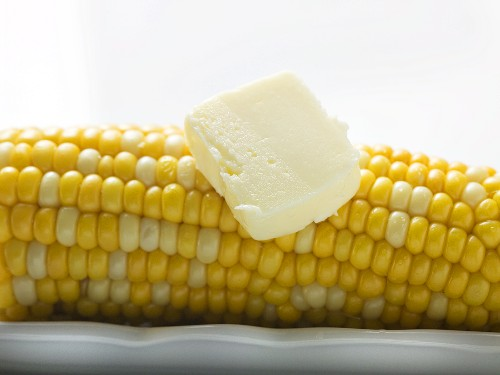 Corn cob with knob of butter (close-up)