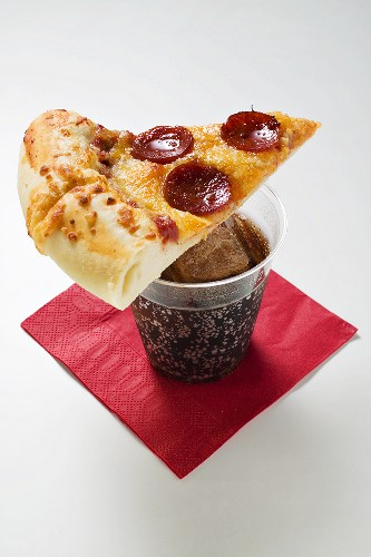 Slice of American-style pepperoni pizza on cola