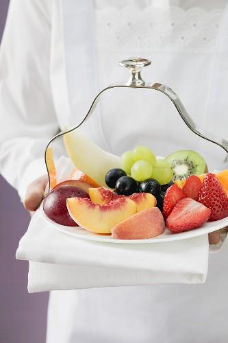 Waitress serving a plate of fruit