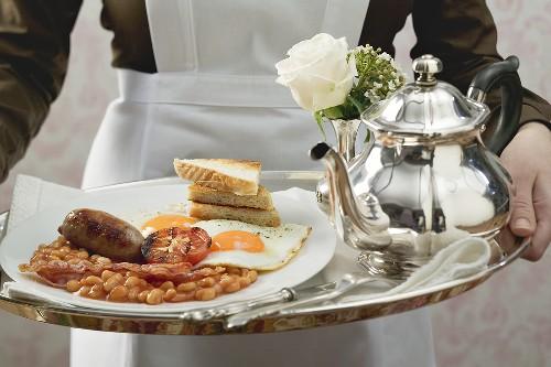 Chambermaid serving English breakfast on tray
