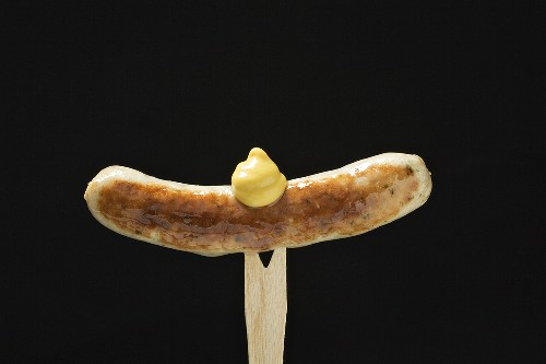 Sausage with mustard on wooden fork