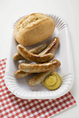Sausages with mustard and bread roll on paper plate