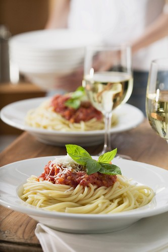 Spaghetti mit Tomatensauce und Weissweingläser auf Tisch