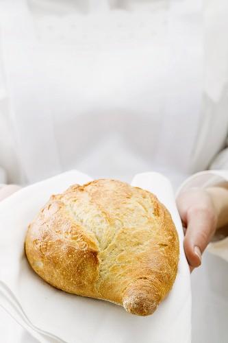 Chambermaid serving bread on fabric napkin