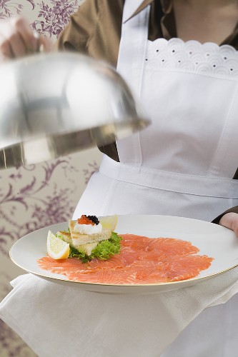 Chambermaid serving smoked salmon with toast