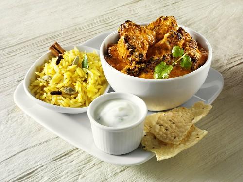 Curry with rice, yoghurt sauce and poppadom (India)
