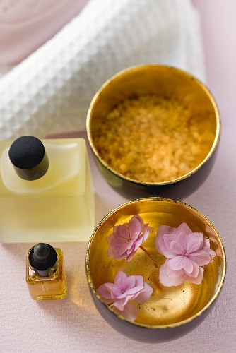 Bath products, flowers in bowl of water, towel
