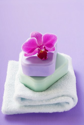 Two bars of soap with orchid on towel