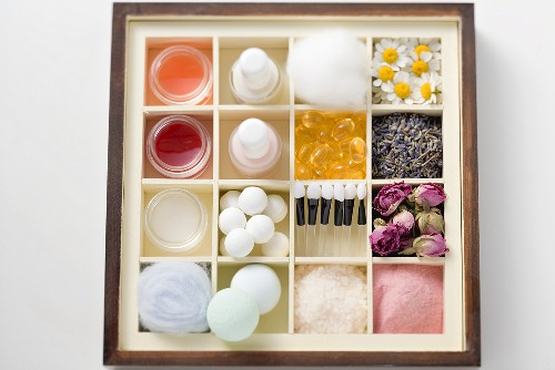 A selection of beauty products and flowers in type case