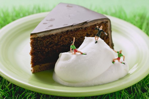 Piece of Sacher torte with cream and football figures