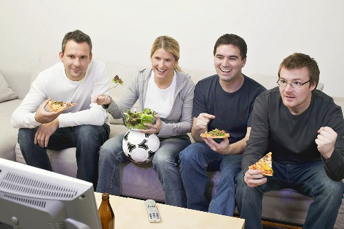 Friends in front of TV with pizza, salad and football