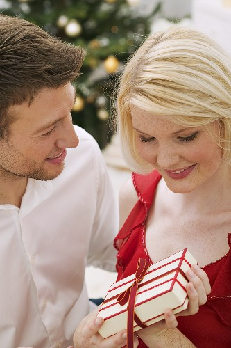 Man giving Christmas gift to woman