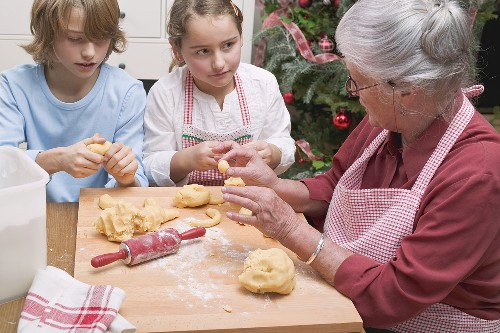 Grandmother telling grandchildren how to shape vanilla crescents