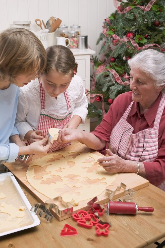 Grandmother showing grandchildren cut-out Christmas biscuit