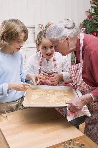 Grandmother showing grandchildren baking tray of Xmas biscuits