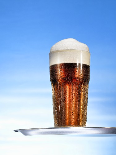 Glass of beer with head on tray