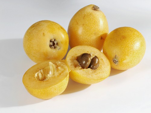 Several loquats, whole and halved