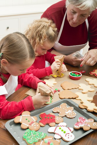Grandmother showing granddaughters how to decorate Xmas biscuits
