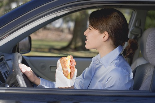 Young woman eating croissant in car