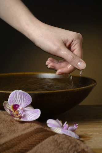 Hand reaching into bowl of water