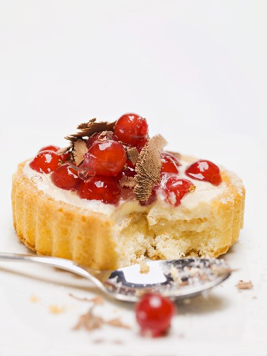 Individual redcurrant flan with chocolate shavings, partly eaten