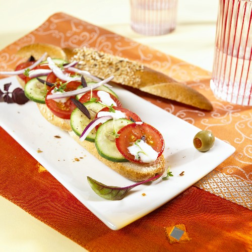 A grain baguette topped with Greek salad