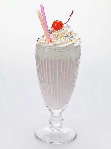Milkshake with cream, sprinkles and cocktail cherry