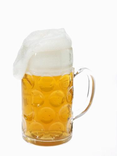 Beer in litre tankard with overflowing foam