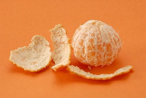 Orange peel lying beside peeled mandarin orange