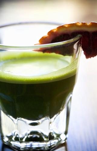 Glass of Wheatgrass Juice with Citrus Garnish