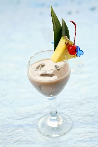 Drink mit Rum, Cassissirup, Ananassaft & Kokosmilch