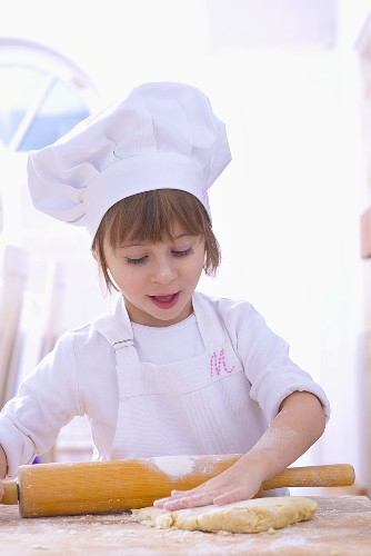 Girl in chef's hat rolling out pastry