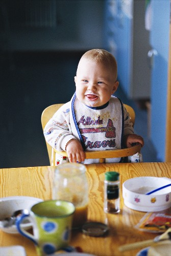 Baby in high chair at dining table