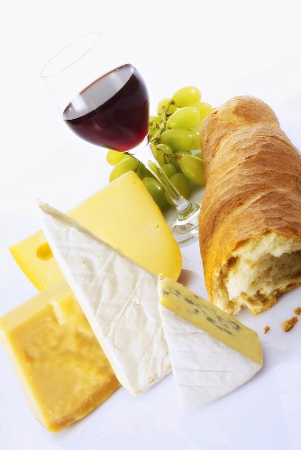 Various cheeses, baguette, glass of red wine and grapes