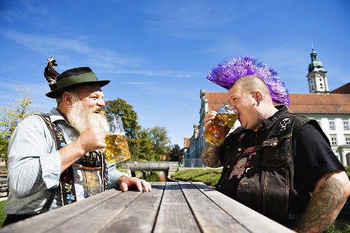 Man with Mohawk hairstyle & man in Bavarian dress in beer garden